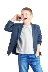 Attractive cute laughing caucasian eight year old boy holding a phone in one hand and putting his other hand in his jeans pocket isolated on white background
